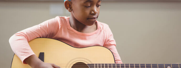 Child practices her guitar at home before a music lesson at Elite Music Academy in North York