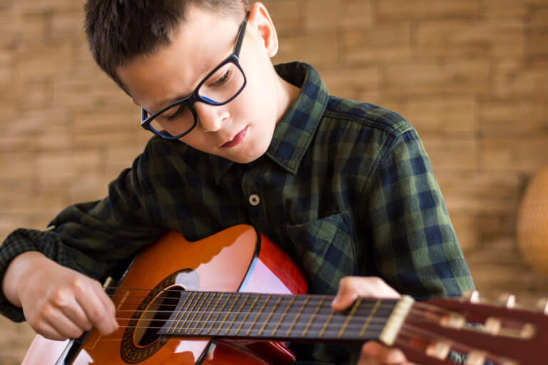 A music student practices guitar at home in Toronto hoping to make his teacher proud